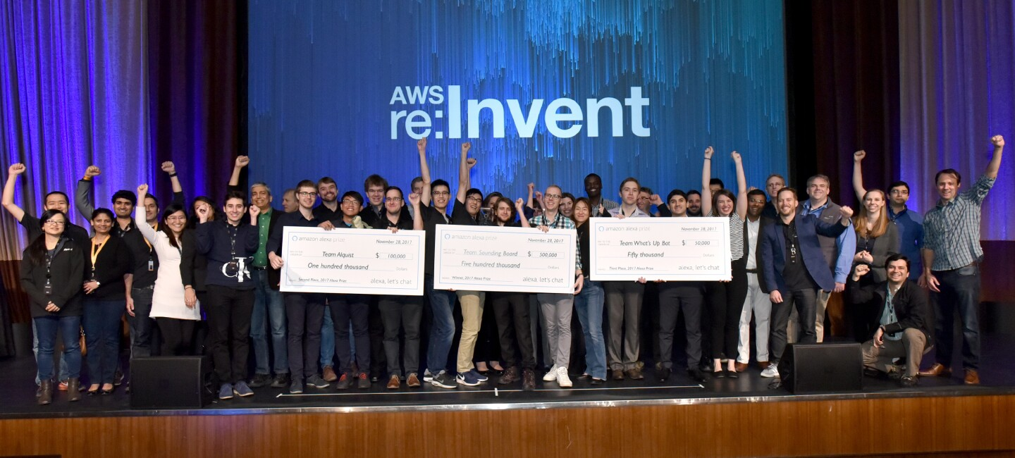 Dozens of students line the state at AWS Re:Invent. Three groups of students are holding prize checks.