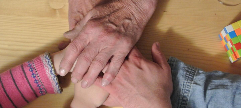 Eine Familie legt ihre Hände aufeinander