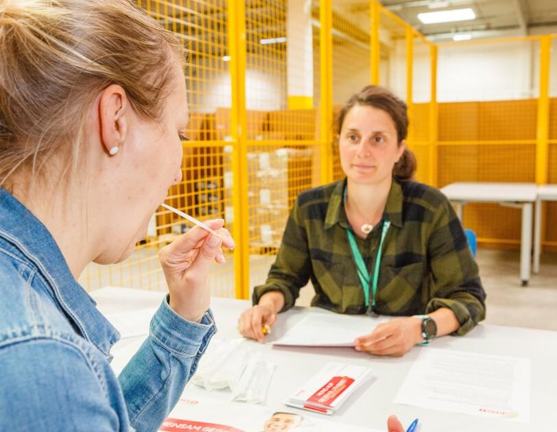 Eine blonde Mitarbeiter lässt sich typisieren - vor ihr hält eine weitere Mitarbeiterin die DKMS-Formulare bereit