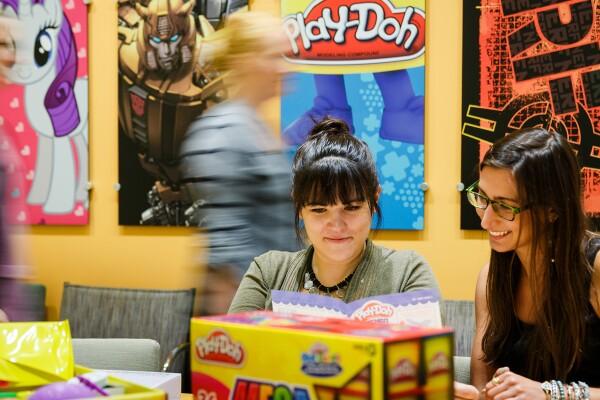 Deux femmes au premier plan sont assises à une table entourée d'emballages. D'autres personnes passent en arrière-plan. Le mur contient des affiches de My Little Pony, Play-Doh et d'autres marques Hasbro.