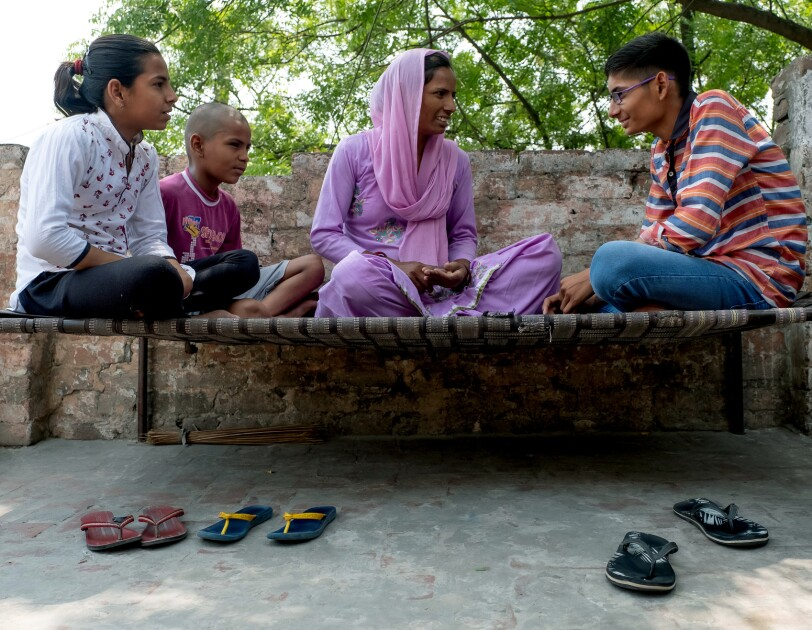 Three children sit outdoors on a bench with their mother. Three pairs of sandals are on the ground in front of the bench. A low brick wall and the leaves of a tree are in the background.