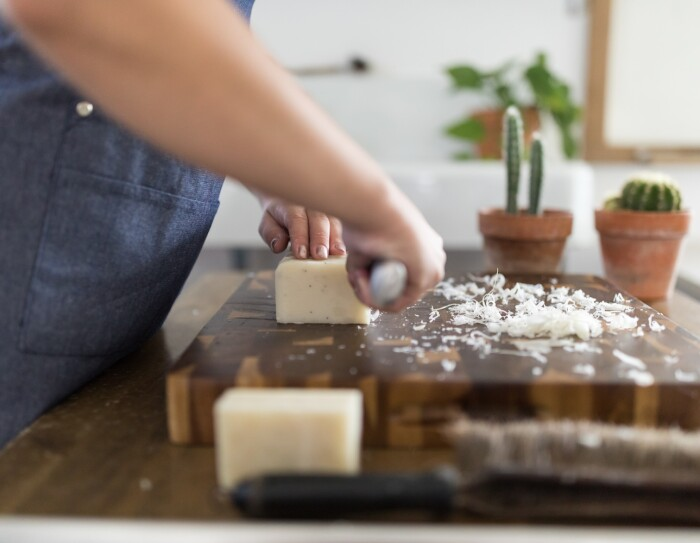 A woman hand-cuts a block of soap on a large, wooden cutting board. In front of the soap block are small bits of shavings from soap cuttings.