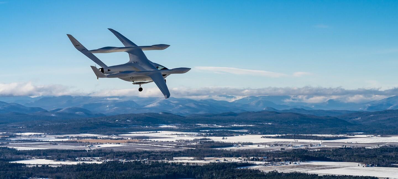 De fondo hay unas montañas nevadas y en primer plano bosque con árboles frondosos y muchos lagos. En primer plano un avión de BETA Technologies de color blanco con una parte inferior como si fuera un helicóptero y por encima unas alas con forma de avión de papel. Se le ve dos ruedas de aterrizaje.