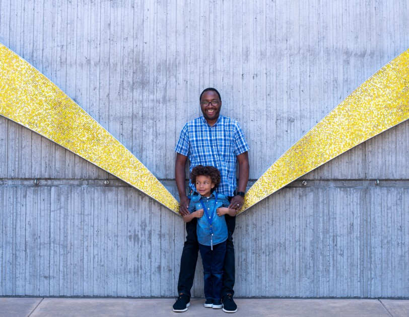 A man stands with a boy in front of a wall decorated with gold arcs.