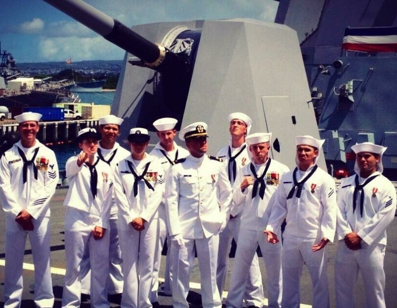 10 members of the U.S. Navy, pose together.