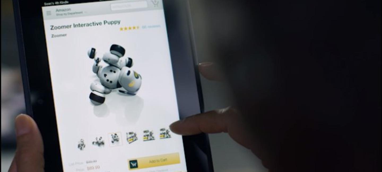 Primer plano de una tablet fire. En la pantalla aparece  la aplicación de Amazon con un producto que es un robot. La mano de una persona que está de espaldas toca la pantalla.