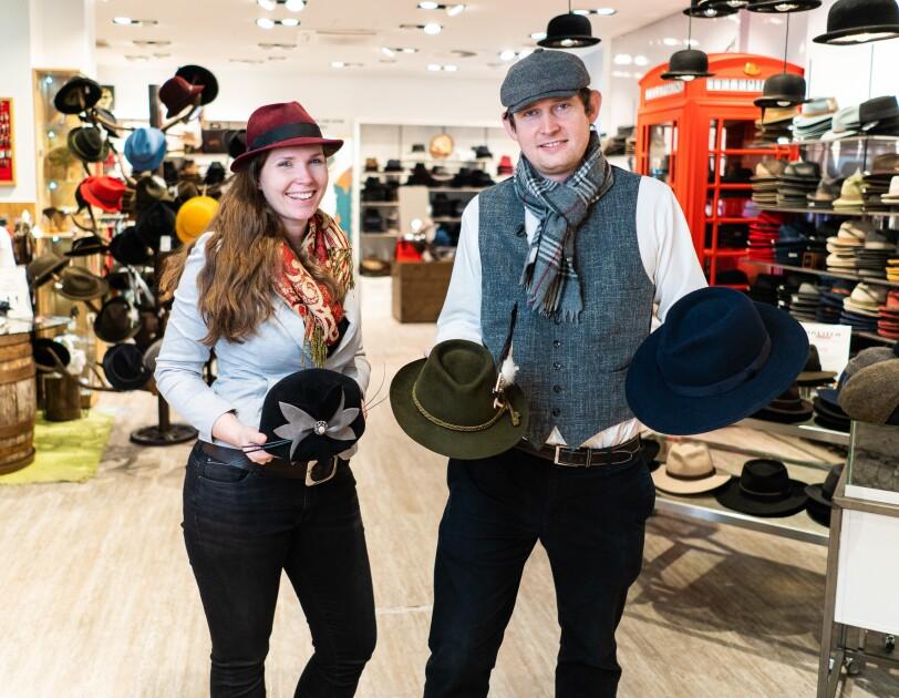 Ein Mann und eine Frau mit Hüten in den Händen stehen in einem Hutladen. Beide tragen Hüte auf dem Kopf. Sie lächeln in die Kamera.