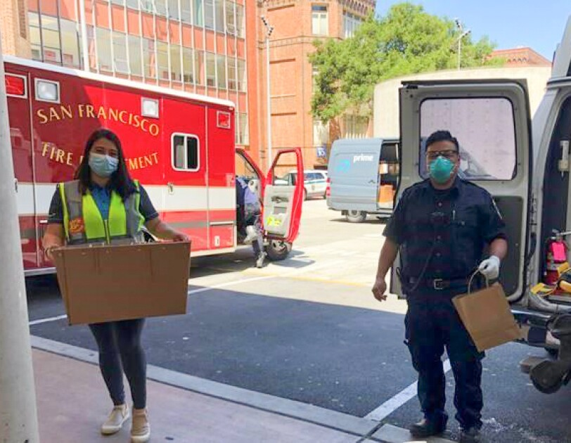 A woman wearing a safety vest and a protective mask carries a box into a fire station.