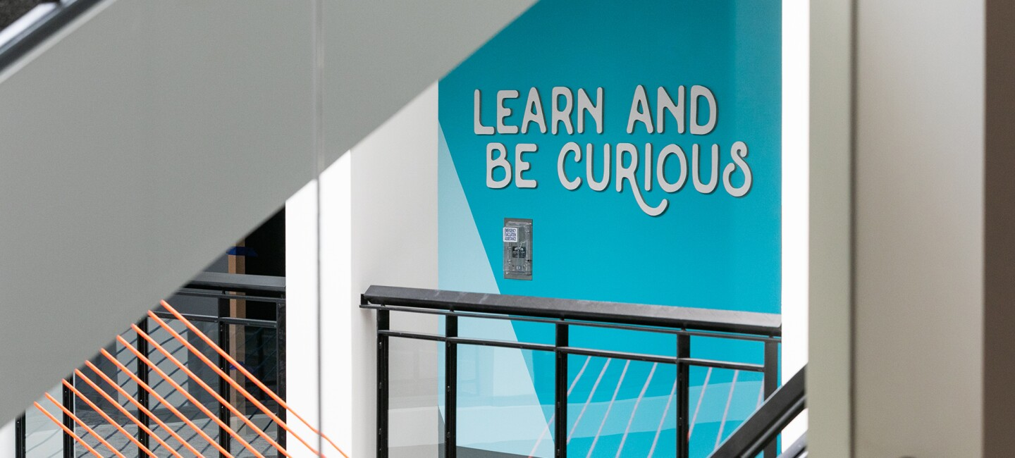 """An office space with a blue wall with the Amazon Leadership Principle """"Learn and be curious"""" in raised white letters on a bright blue background."""