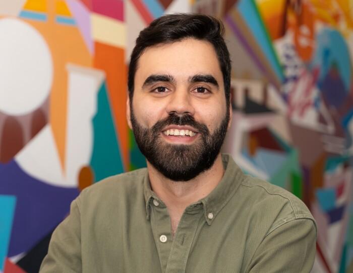 Alexandre Rodríguez, New Account Manager, Channels Sales. Mirando a cámara con una camisa color verde camuflaje. Tiene el pelo negro, barba y bigote.