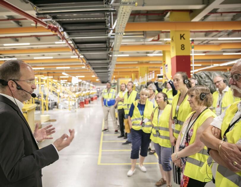 Ein Herr im grauen Anzug steht vor einer Gruppe von Besuchern in gelben Sicherheitswesten.