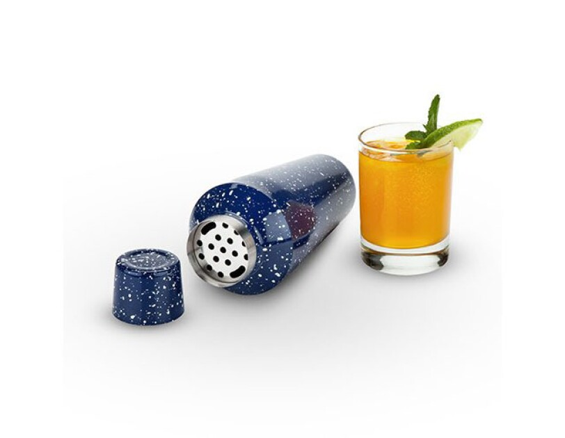 Speckled blue camp-style cocktail shaker lies on its side. To the right is a cocktail in a lowball glass with lime slice and mint leaf.