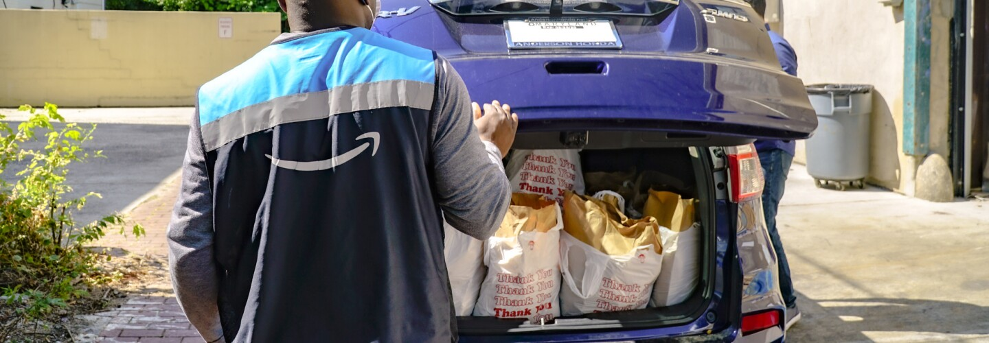 A man in a vest with the Amazon smile logo closes the back of a car filled with bags of groceries.