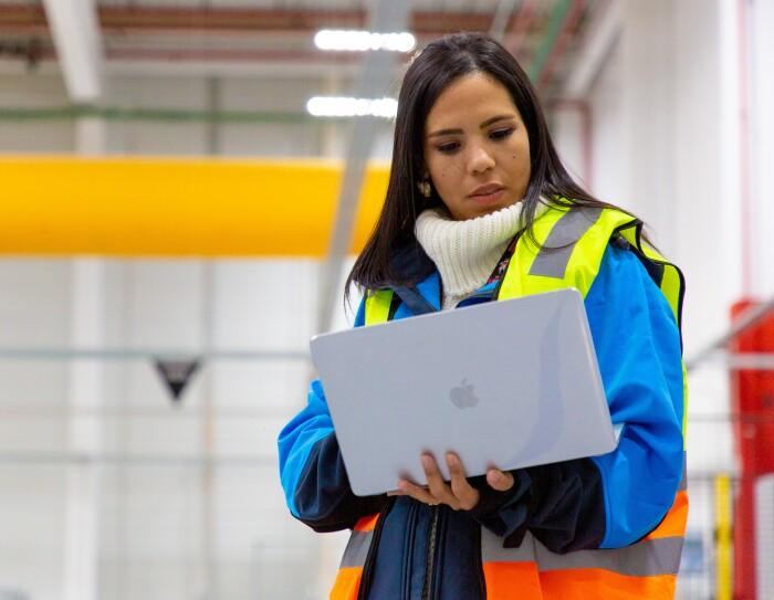 Ivette Duran, CEO de Cainaima Logistics, de pie con un ordenador entre las manos. De fondo está el centro logístico de color blanco y amarillo. Ella es morena y tiene el pelo largo y negro. Lleva un jersey de color blanco y de cuello alto, una chaqueta azul y un chaleco fluorescente.