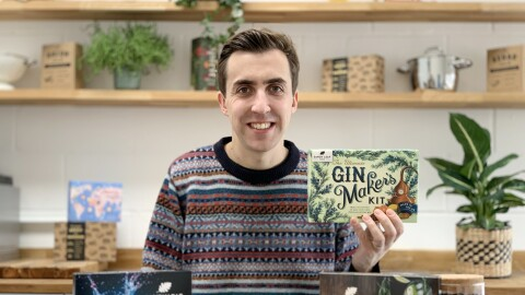 Scott MacDonald from Sandy Leaf Farm at a table with the gin making kits in front of him. He is also holding a box containing the products.