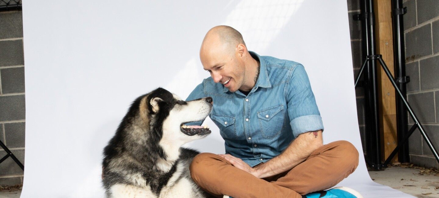 A man and his dog sit on a photography backdrop, smiling at each other.