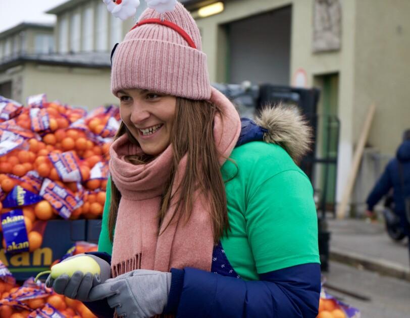 Eine junge Frau im grünen Shirt bei der Ausgabe von Obst