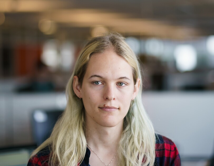 Danielle Skysdottir in an office space with cubicles in the background. She has long blond hair and wears a T-shirt, a flannel shirt, and a necklace with a pendant.