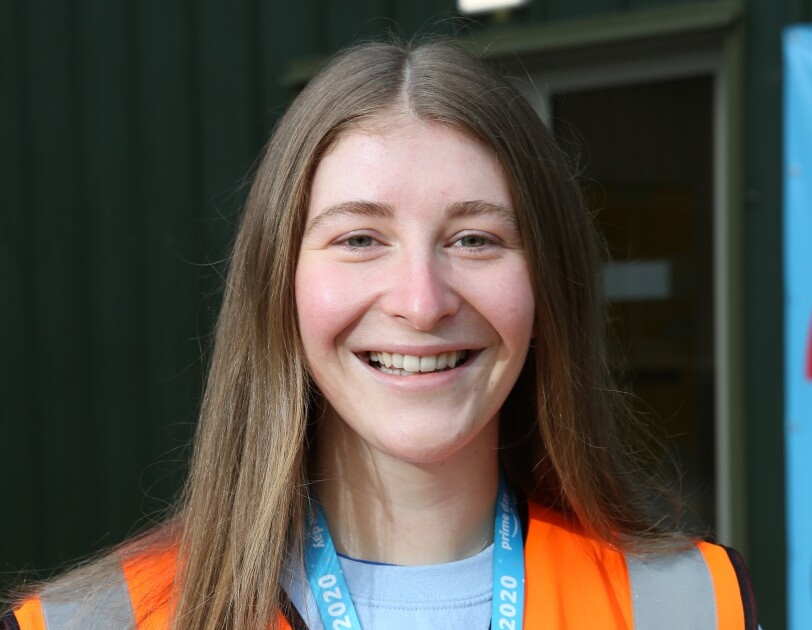 Fran Williams-Tanton smiling standing outside of the fulfilment centre she works at while wearing a high-vis jacket.