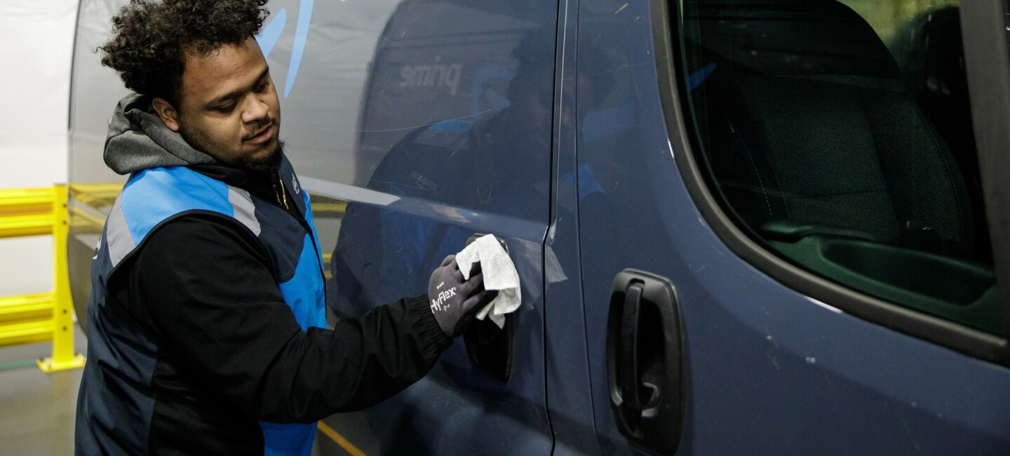 A man uses a disinfecting wipe to clean a door handle on a delivery van.