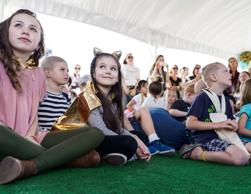 Dozens of children sit together on turf, inside a large white tent, at an Amazon #GoGold event. Some of the children wear gold items, including capes, bracelets, pins, and more.