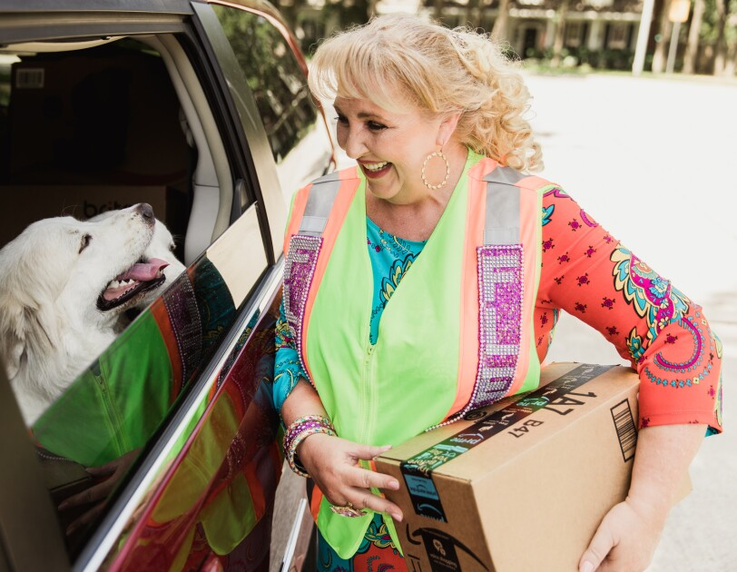 A woman in a bedazzled Amazon Flex vest is smiling and standing with her two white dogs.