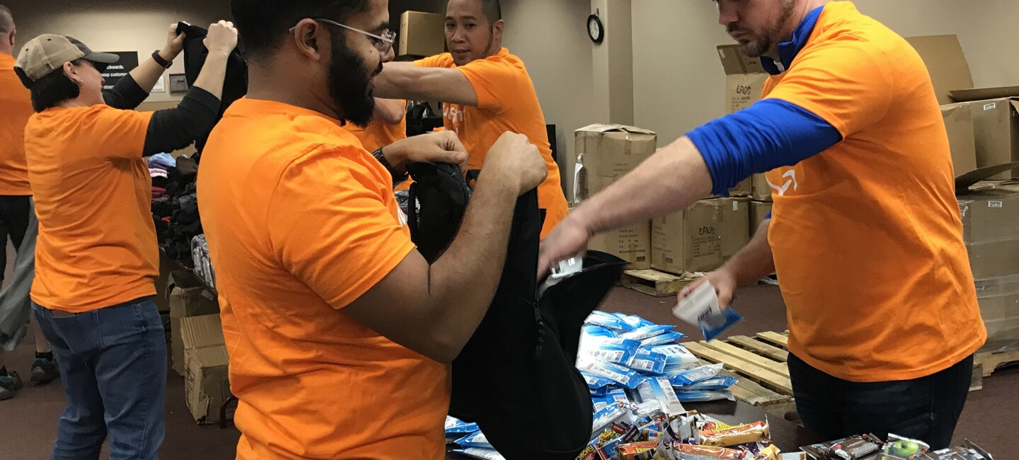 Amazon associates filling backpacks with essential items