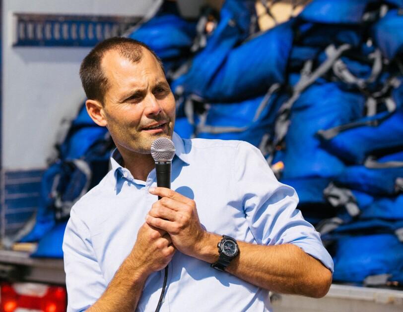 Ein Mann im blauen Hemd hält ein Mikrofon.