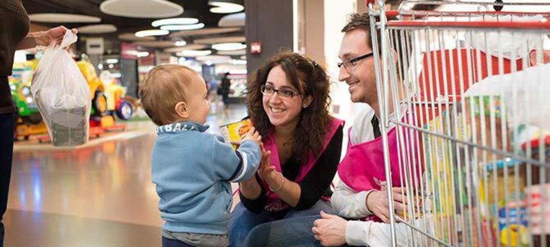 Un homme et une femme employés d'Amazon portant un brassard Restos du Coeur sourient à un bébé dans un centre commercial. Un caddie de courses alimentaires apparaît en premier plan