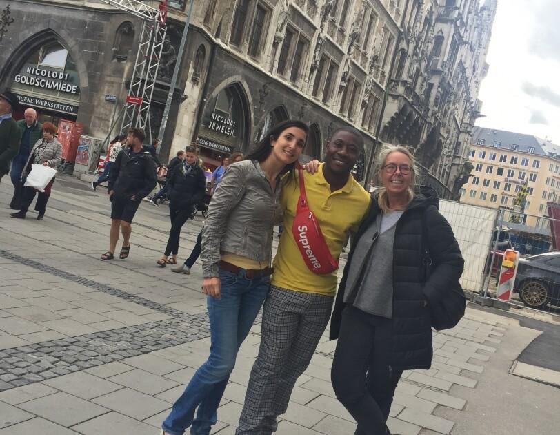 Drei Personen stehen gemeinsam in der Münchner Fußgängerzone.