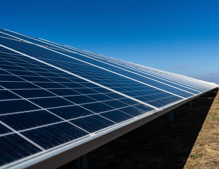 Primera plano de placas solares. El suelo es de tiera con hierbas de color verde y marrón. El cielo es azul.