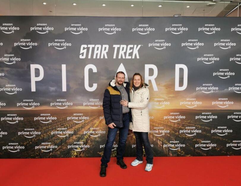 Ein Pärchen auf dem roten Teppich. Im Hintergrund eine Foto-Leinwand mit Aufdruck Star Trek PICARD.