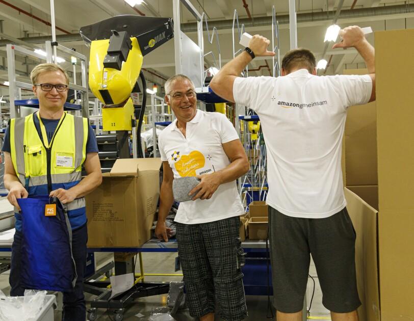 """3 Mitarbeiter verpacken Schuluntensilien: Alle 3 lächeln. Ein der Mitarbeiter ist von hinten zu sehen, er deutet mit beiden Daumen auf den T-Shirt-Aufdruck am Rücken """"Amazon gemeinsam""""."""