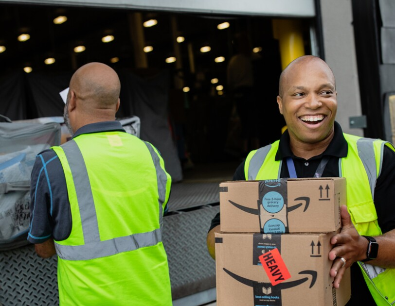 A smiling man holds boxes while people in the background load a truck.