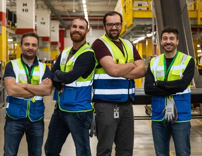 Quattro uomini con gilet ad alta visibilità e le braccia incrociate, guardano in camera e sorridono. Sono nel centro di distribuzione Amazon di Passo Corese.