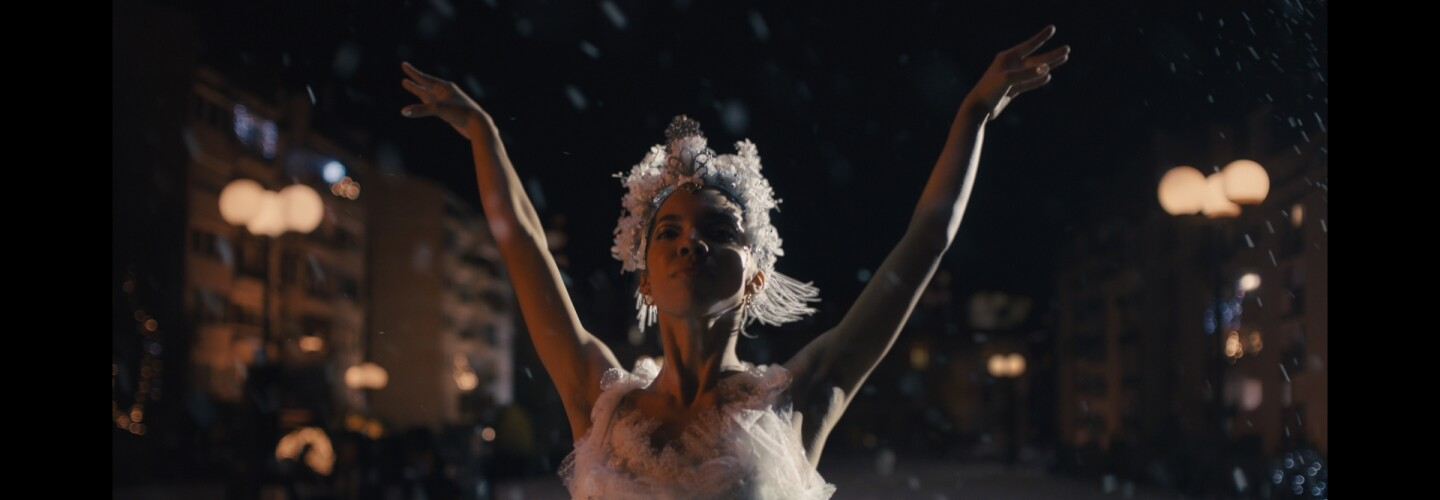 Ballerina dressed in white feathers and arms in the air