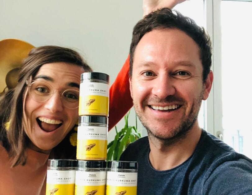 Ein Mann und eine Frauh lachen in die Kamera. Sie halten vor sich einen Stapel voller Dosen mit einem gelben Etickett und einem schwarzen Deckel.