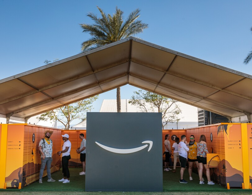 Amazon Lockers under a large tent with palm trees in the background. The Amazon smile logo is at the center of the image.
