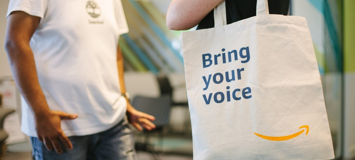 "Immagine che mostra persone all'interno di una sede Amazon con shopper in primo piano con scritta ""Bring your voice"""