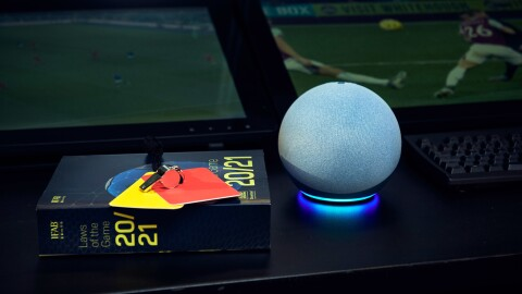The Echo Dot on a table with a book of football rules and a red and yellow card