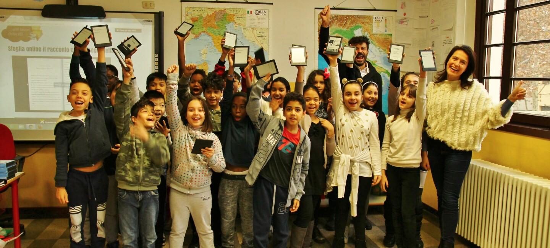 Un gruppo di bambini nella loro aula scolastica regge in mano dei dispositivi Kindle.