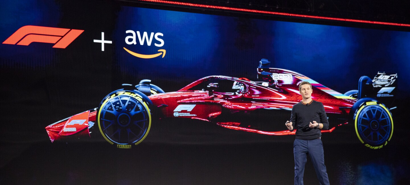 Rob Smedley, Formula 1 engineer standing on stage at the AWS re:Invent 2019 event. He is in front of a large screen with a Formula 1 car on it.