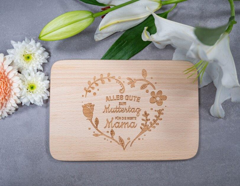 """Auf einem grauen Tisch liegt ein Holzbrett mit der Aufschrift """"Alles Gute zum Muttertag für die beste Mama"""""""