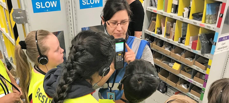 """Eine dunkelhaarige Amazon Mitarbeiter mit blauer Sicherheitsweste ist von Kindern in gelten Sicherheitswesten mit Aufdruck """"Besucher"""" umringt: Sie zeigt auf den Scanner, dessen Funktionsweise sie gerade erklärt."""