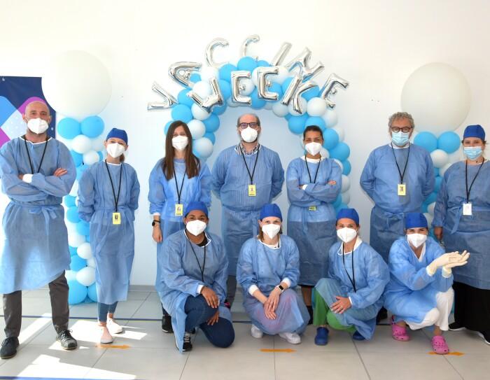 Un gruppo di medici in tute protettive blu posa davanti a due archi di palloncini bianchi e blu con la scritta 'Vaccine Week' alle loro spalle