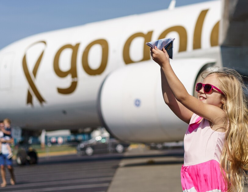 """An aircraft with custom messaging applied to it, stating """"go gold ...because kids can't fight cancer alone."""" In front of the airplane, is a young girl with long blonde hair, pink sunglasses and a pink dress flying a paper airplane."""