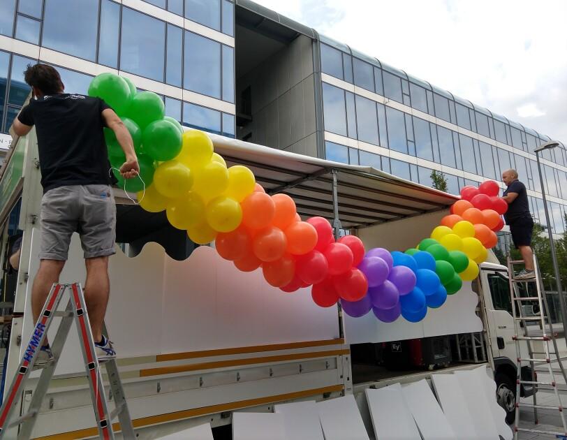 Zwei Männer stehen auf Leitern und befestigen Luftballons am Glamazon-Wagen.