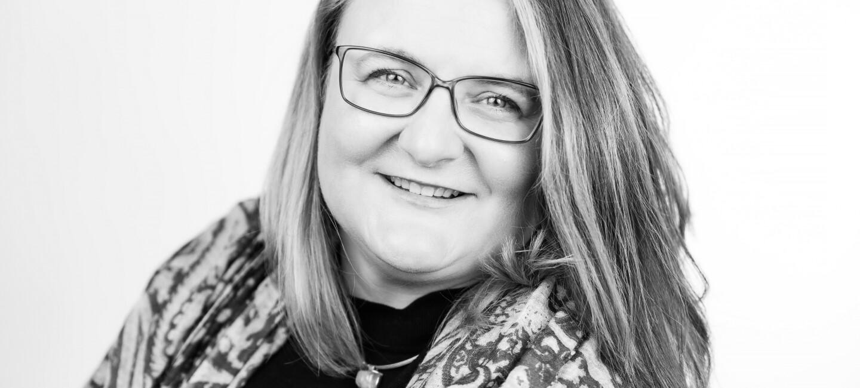 Amazon Europa-Direktorin Ingrid Ebner im sw Porträt: Eine Frau mit halblangen blonden Haaren und Brille blickt lächelnd in die Kamera.