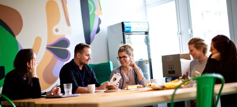 Mitarbeiter sitzen im Bür an einem großen Gemeinschaftstisch, unterhalten sich, trinken Kaffee. Die Umgebung ist bunt gestaltet mit grünen Stühlen und farbigen Wänden.