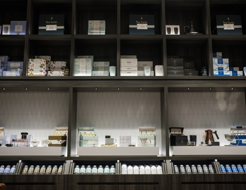 Shelves containing a variety of packaged products as well as teacups and teapots.